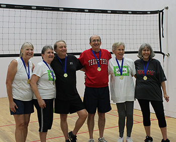 Seven people wearing medals standing at the volleyball net.