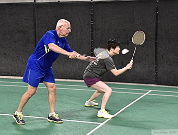 Man and woman playing badminton.