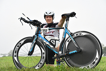 Man kneeling beside bicycle.