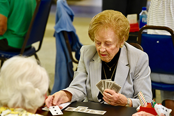 Women playing bridge card game.