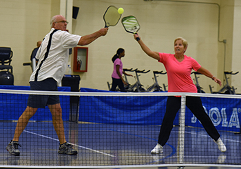 Man and woman playing pickleball.