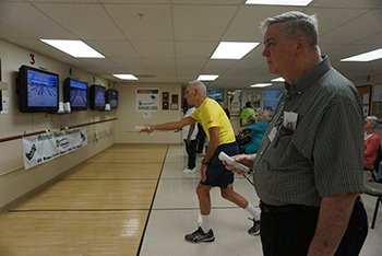 Men playing wii bowling.