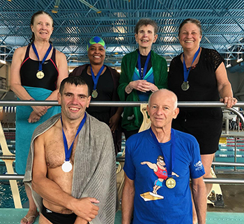 Six people with medals for diving.