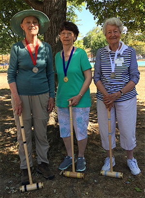 Three women with croquet mallets.