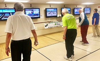 Four wii bowlers playing the game.